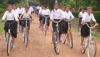 Cambodia - Children riding to school on bikes.